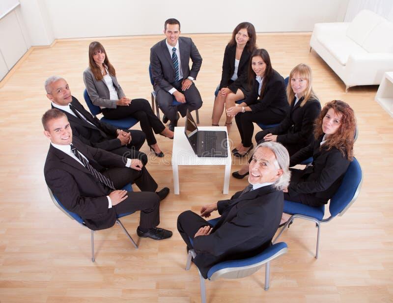 Grupp av affärsfolk som sitter på stolar royaltyfria bilder