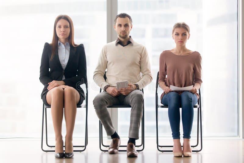 Grupp av affärsfolk som sitter på stolar som ser kameran arkivfoton