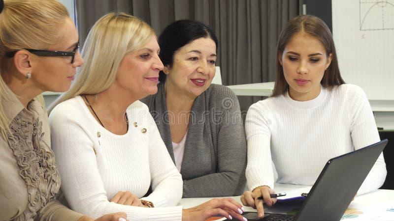 Grupp av affärskvinnor som tillsammans använder bärbara datorn på kontoret royaltyfri foto