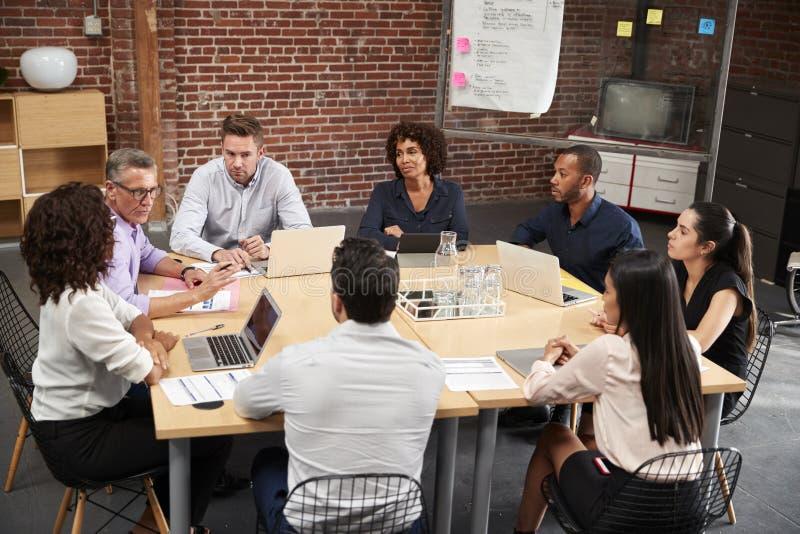 Grupp av affärsmän och affärskvinnor som möter runt om kontorstabellen arkivbilder