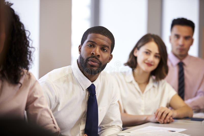 Grupp av affärsmän och affärskvinnor som sitter på tabellen som lyssnar till presentationen i modernt kontor arkivfoto