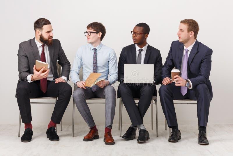Grupp av affärsmän som sitter på stolar royaltyfri fotografi