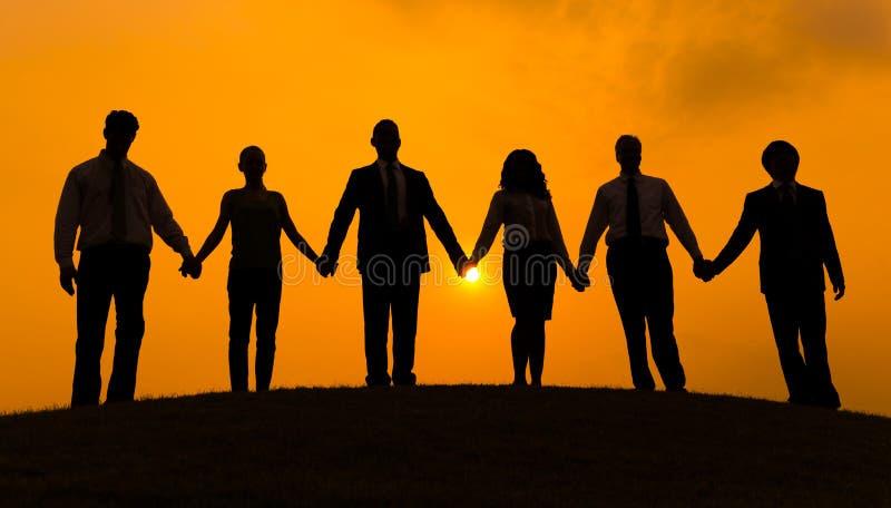 Grupp av affärspartnerhållhanden tillsammans i kontur med soluppgångbakgrund arkivfoto