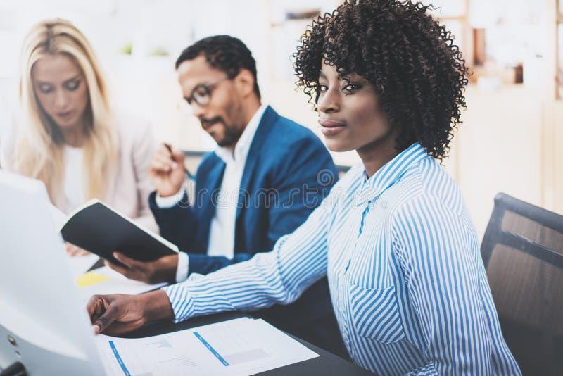 Grupp av affärspartners som tillsammans arbetar på online-bankrörelseprojekt i modernt kontor Ung attraktiv afrikansk kvinna som  royaltyfri fotografi