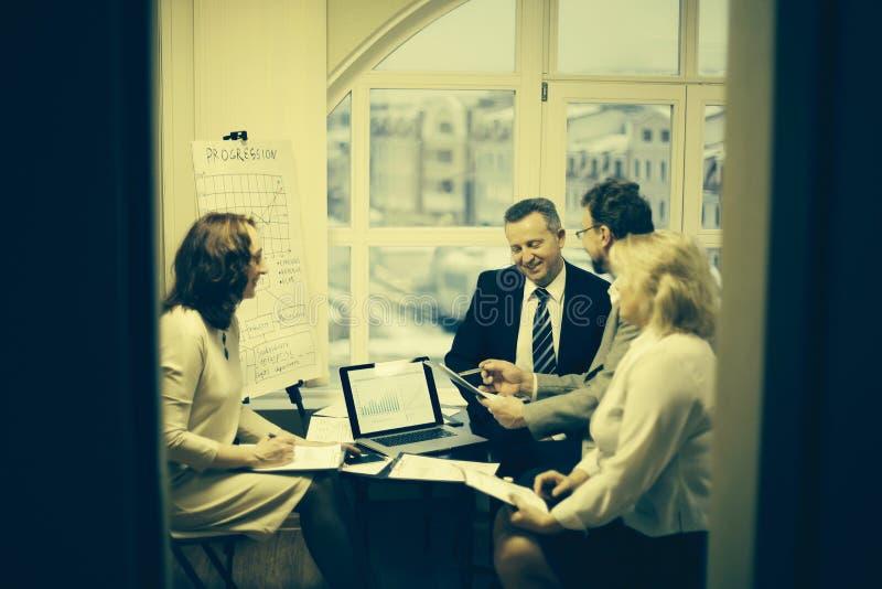 Grupp av aff?rsfolk som diskuterar ett viktigt dokument royaltyfri fotografi