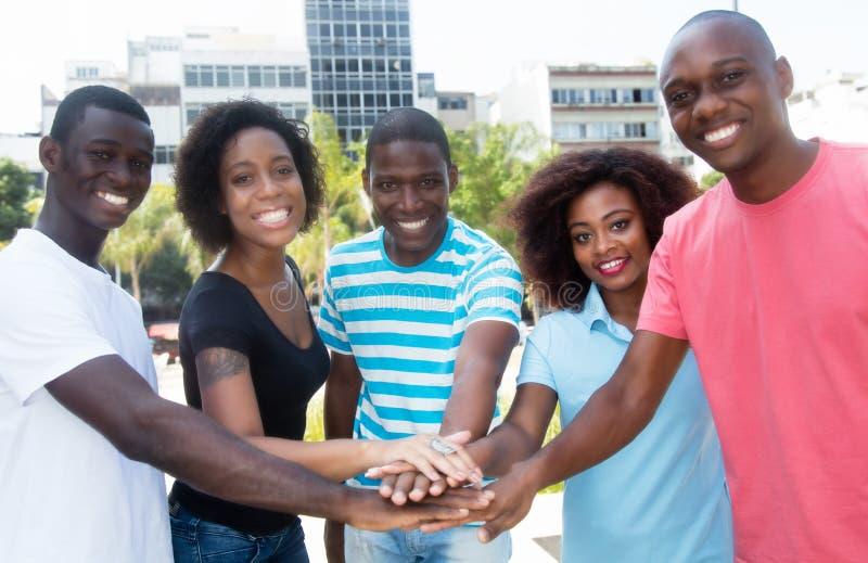 Grupp av afrikansk amerikanmän och kvinnor som tillsammans sätter händer arkivfoto