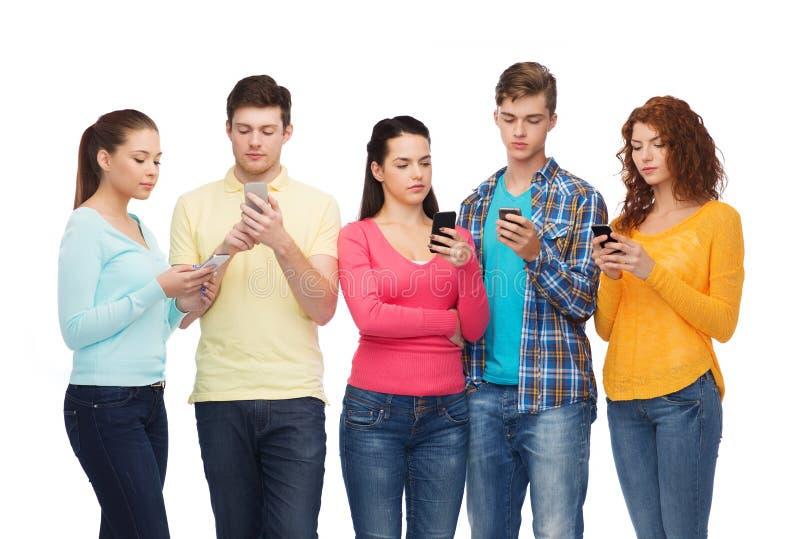 Grupp av allvarliga tonåringar med smartphones royaltyfri fotografi