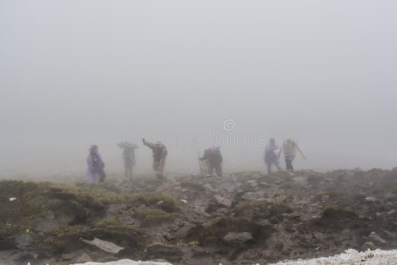 Grupp av alpinister som klättrar upp på överkanten av berget royaltyfri bild