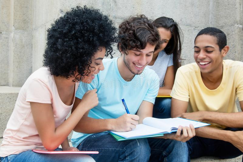 Grupp av amerikanska studenter som utomhus lär på universitetsområde arkivbild