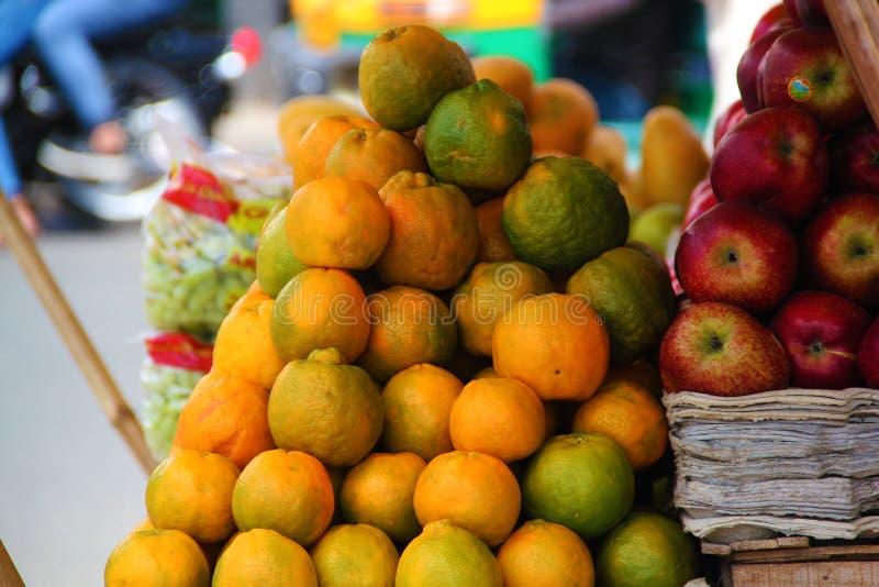 Grupp av apelsiner och äpplen på gatan royaltyfri fotografi