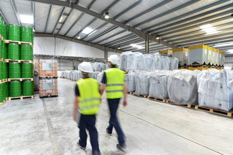 Grupp av arbetare i logistikbranscharbetet i ett lager w arkivbilder