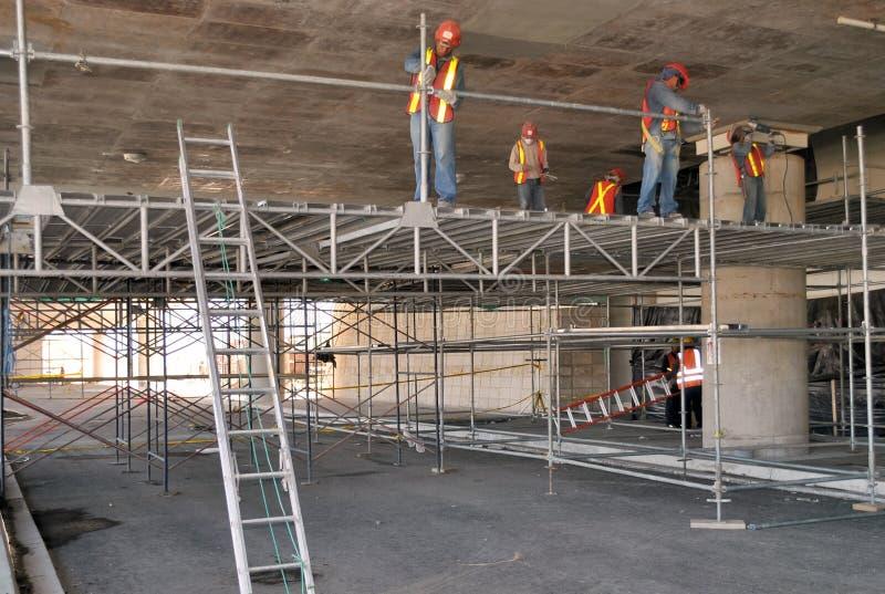 Grupp av arbetare som monterar materialet till byggnadsst?llning i deras workspace arkivbild