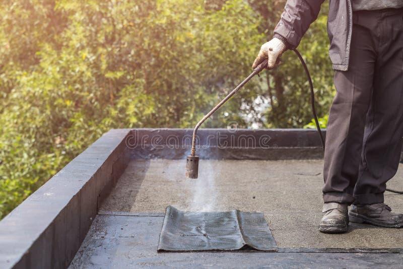 Grupp av arbetaren som installerar tjärafolie på taket av byggnad arkivbild