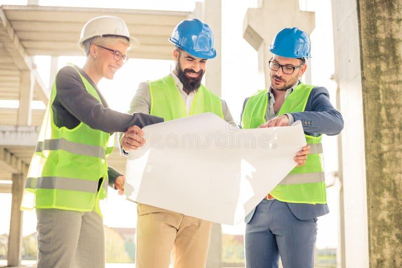 Grupp av arkitekter eller affärspartners som möter på en konstruktionsplats arkivbild