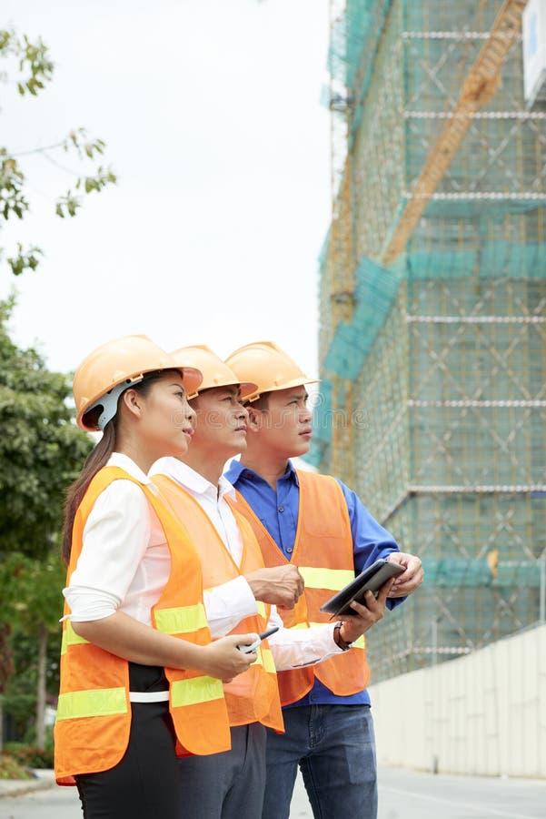 Grupp av arkitekter som arbetar på konstruktionsplats arkivbild