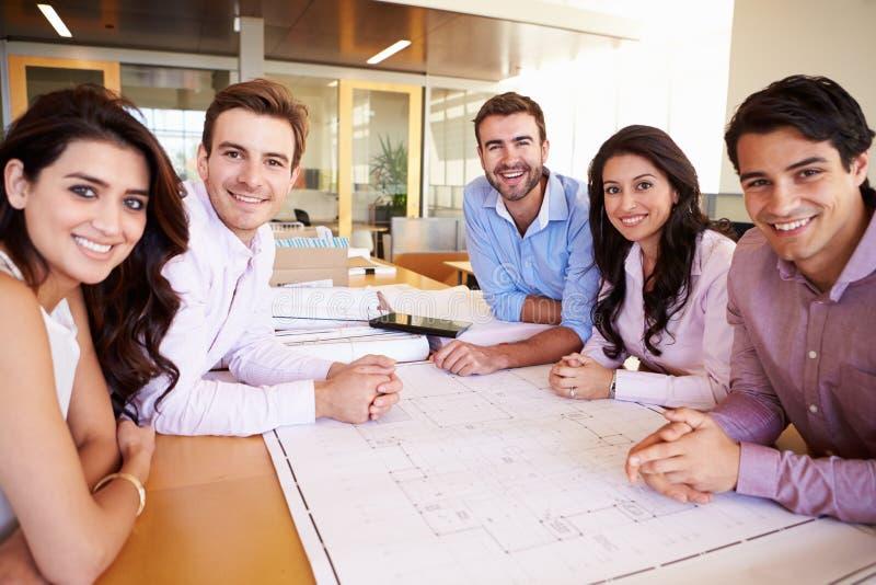 Grupp av arkitekter som diskuterar plan i modernt kontor fotografering för bildbyråer