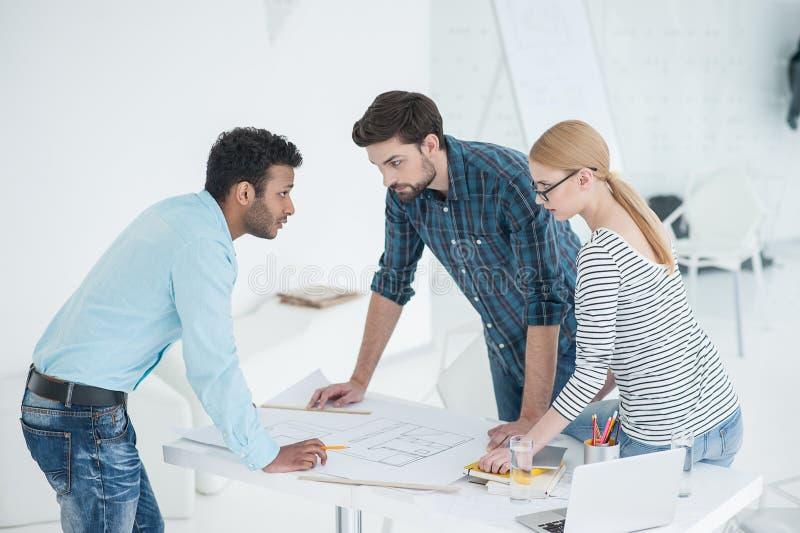 Grupp av arkitekter som diskuterar plan i modernt kontor arkivfoton