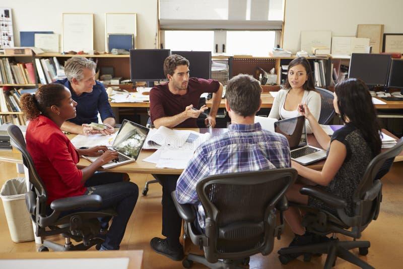Grupp av arkitekter som möter runt om skrivbordet arkivfoton