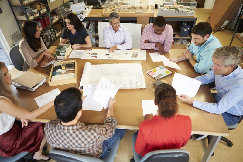 Grupp av arkitekter som sitter runt om tabellen som har möte royaltyfria bilder