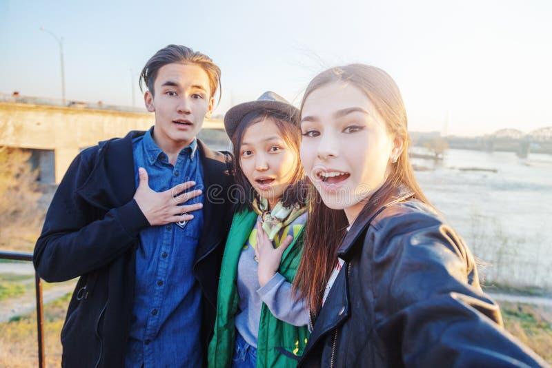 Grupp av asiatisk ton?r som tar selfie p? telefonen och att ha gyckel, b?sta v?n och digitalt utvecklingsbegrepp arkivfoto