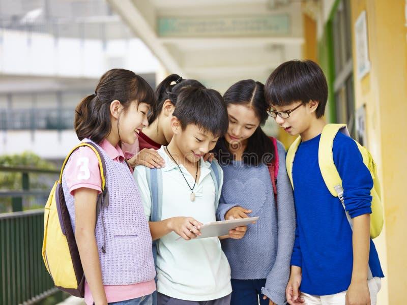 Grupp av asiatiska elever som använder minnestavladatoren på skolan royaltyfria bilder