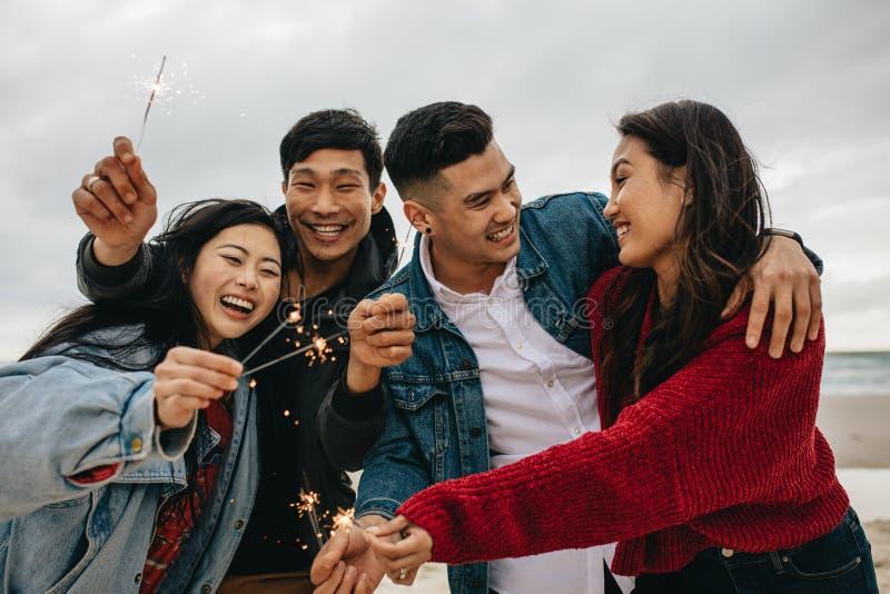 Grupp av asiatiska vänner som firar nytt års den ay stranden för dag royaltyfri bild