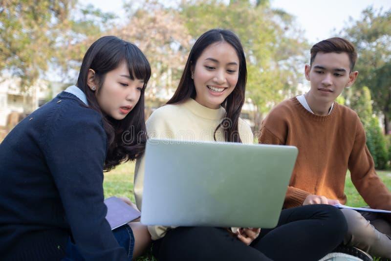 Grupp av asiatiskt sammanträde för universitetsstudenter på det gröna gräset W royaltyfri bild