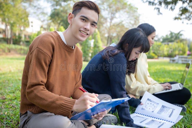 Grupp av asiatiskt sammantr?de f?r universitetsstudenter p? arbetet och l?sningen f?r gr?nt gr?s utanf?r tillsammans i en parkera royaltyfri foto