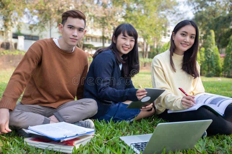Grupp av asiatiskt sammantr?de f?r universitetsstudenter p? arbetet och l?sningen f?r gr?nt gr?s utanf?r tillsammans i en parkera royaltyfria bilder