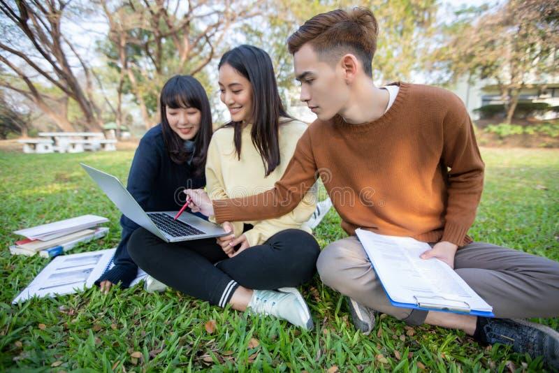 Grupp av asiatiskt sammantr?de f?r universitetsstudenter p? arbetet och l?sningen f?r gr?nt gr?s utanf?r tillsammans i en parkera royaltyfri bild