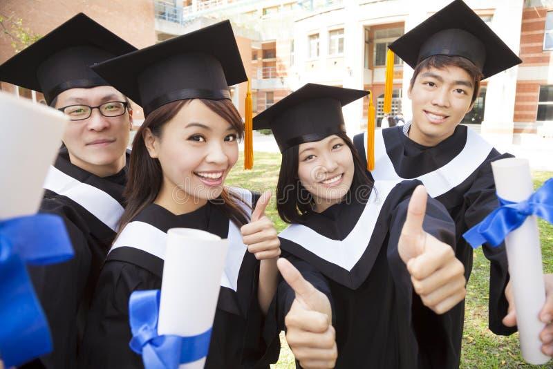 Grupp av att avlägga examen studenter som rymmer diplomet och tummen-upp fotografering för bildbyråer