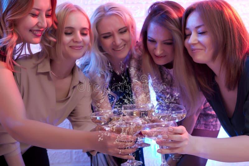 Grupp av att festa flickor som klirrar flöjter med brusandeseger royaltyfria bilder