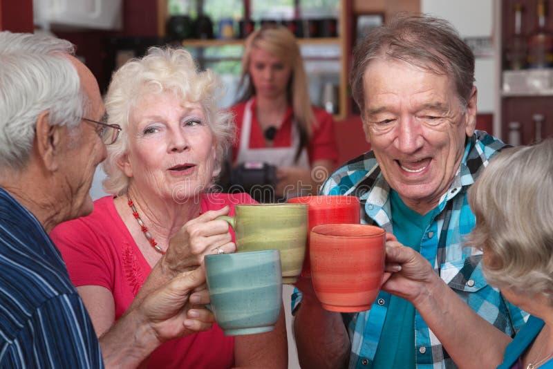 Grupp av att fira för fyra pensionärer fotografering för bildbyråer