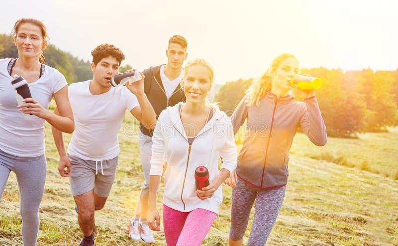 Grupp av att jogga folkdricksvatten arkivfoto