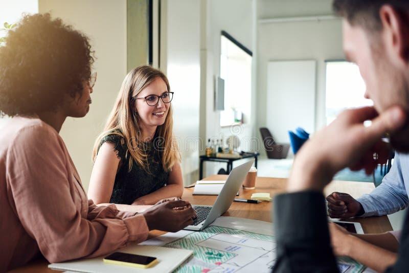 Grupp av att le businesspeople som tillsammans möter i ett kontor bo royaltyfria bilder