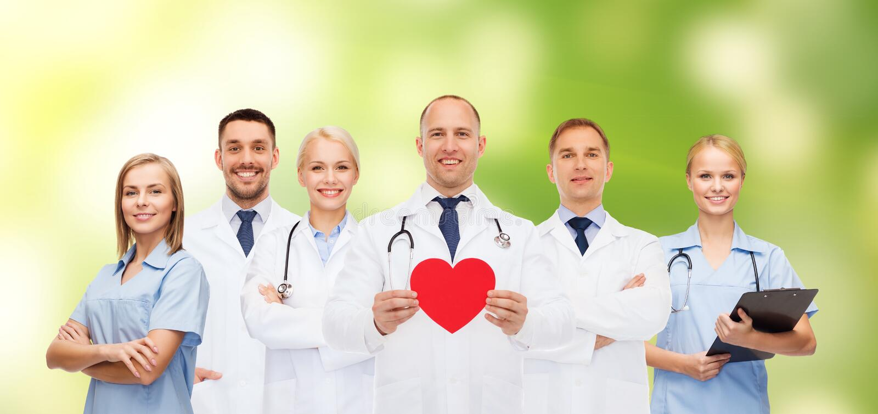 Grupp av att le doktorer med röd hjärtaform arkivfoton