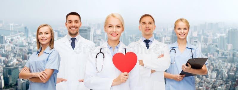 Grupp av att le doktorer med röd hjärtaform royaltyfri foto