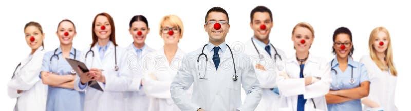 Grupp av att le doktorer på den röda näsdagen arkivbilder