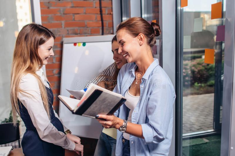 Grupp av att le flickvänner som skrattar, medan studera och revidera för examen i arkiv fotografering för bildbyråer