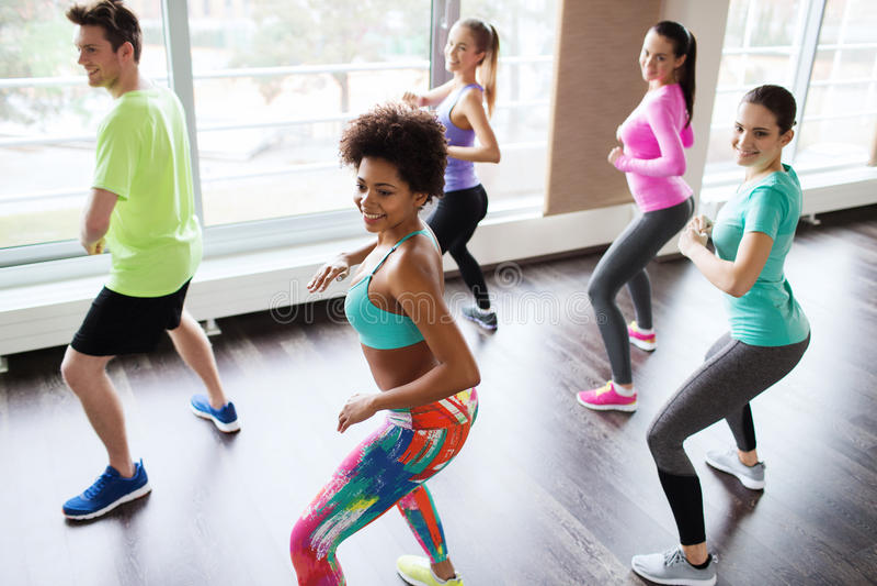 Grupp av att le folk som dansar i idrottshall eller studio arkivbild