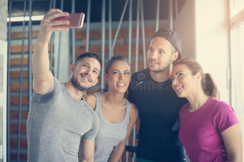 Grupp av att le folk som gör själv-bilden i idrottshall P arkivfoton