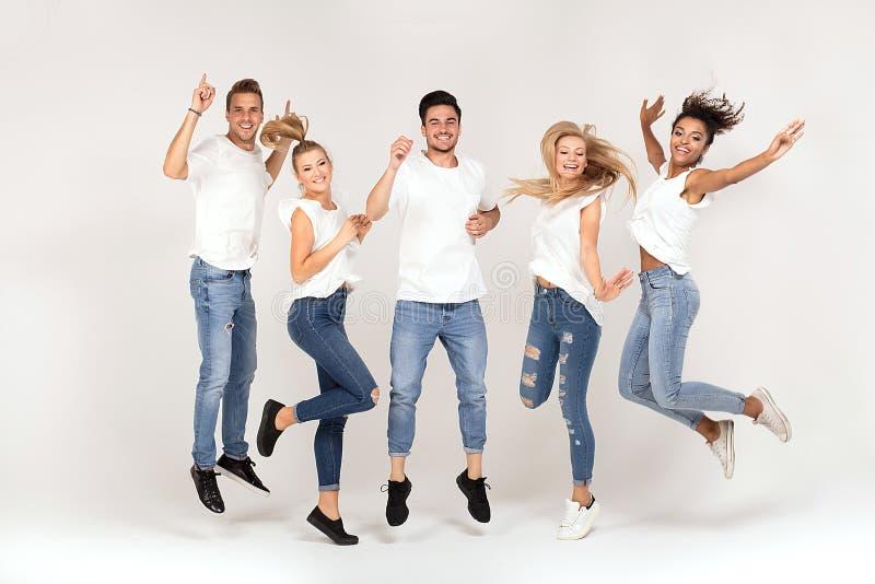 Grupp av att le folk som tillsammans hoppar och att ha gyckel arkivfoto