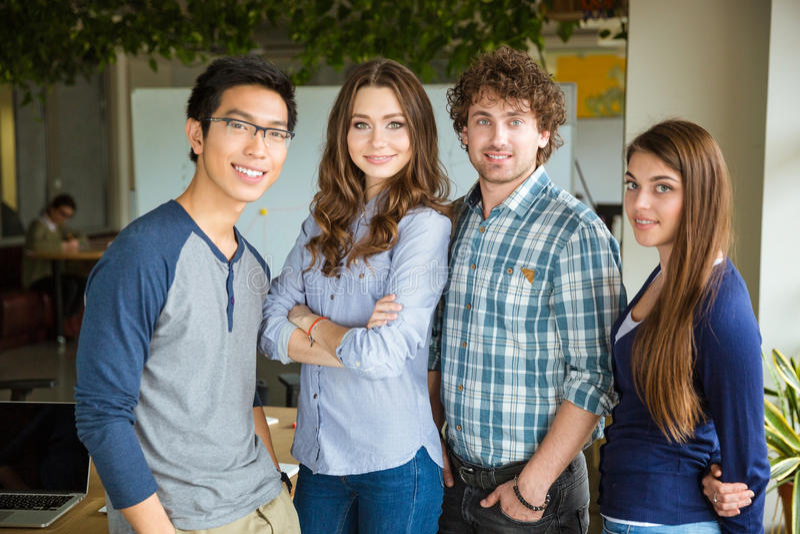 Grupp av att le härliga nöjda säkra studenter som tillsammans står royaltyfria foton