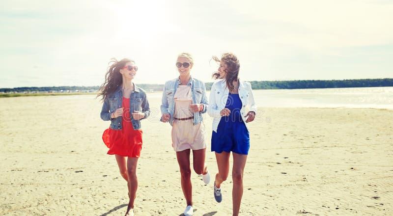 Grupp av att le kvinnor i solglasögon på stranden arkivbild