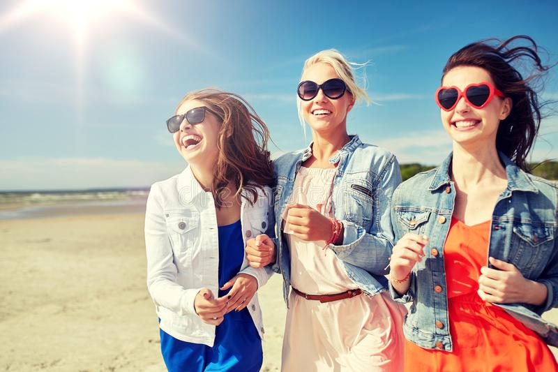 Grupp av att le kvinnor i solglasögon på stranden royaltyfri foto