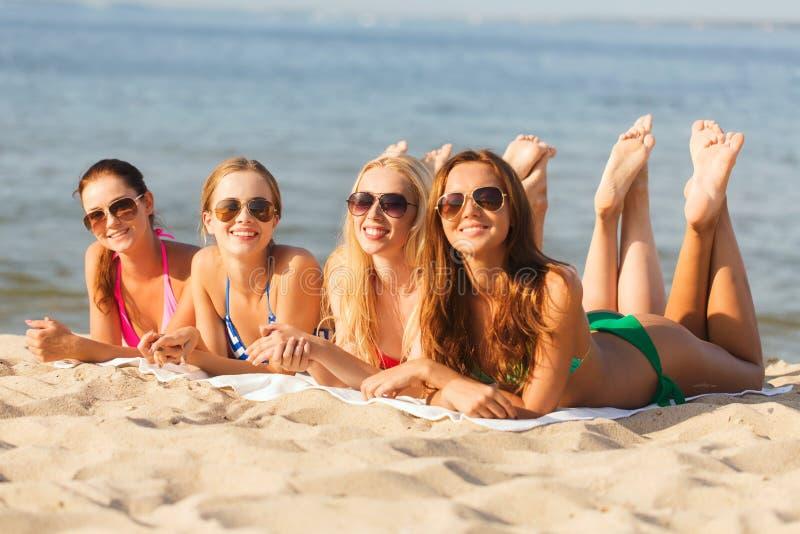 Grupp av att le kvinnor i solglasögon på stranden arkivbilder
