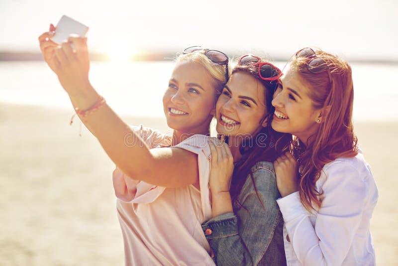 Grupp av att le kvinnor som tar selfie på stranden royaltyfri bild