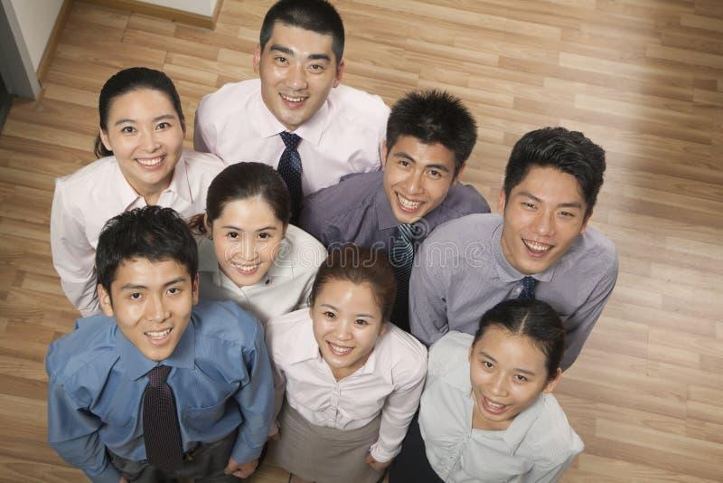 Grupp av att le och lyckliga coworkers som ser upp på kameran, stående, fast utgiftskott fotografering för bildbyråer
