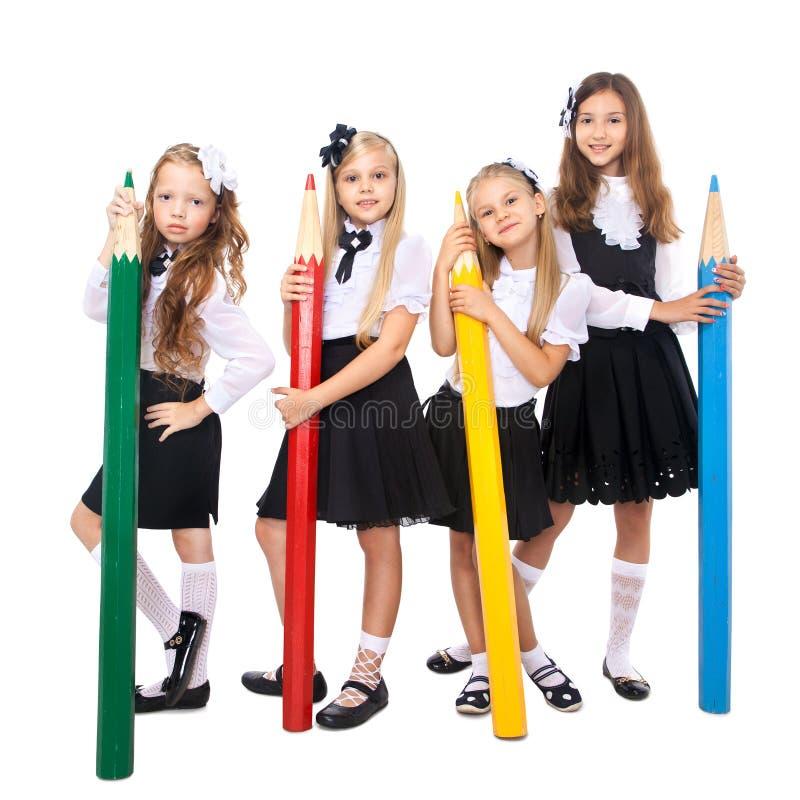 Grupp av att le skolflickor med stora kulöra blyertspennor arkivfoton