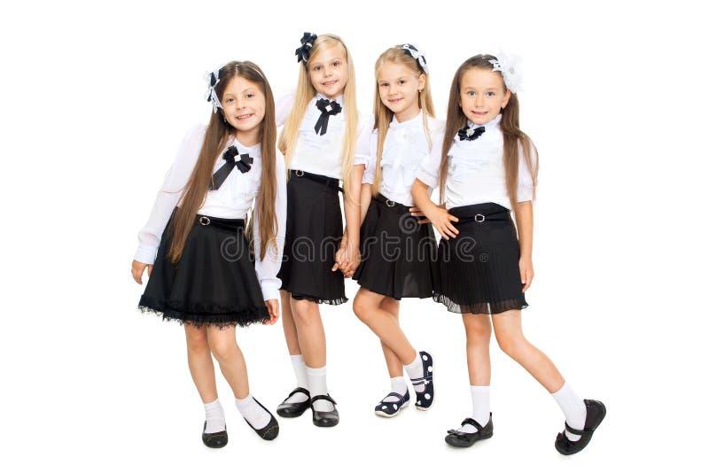 Grupp av att le skolflickor som isoleras på vit bakgrund arkivfoto